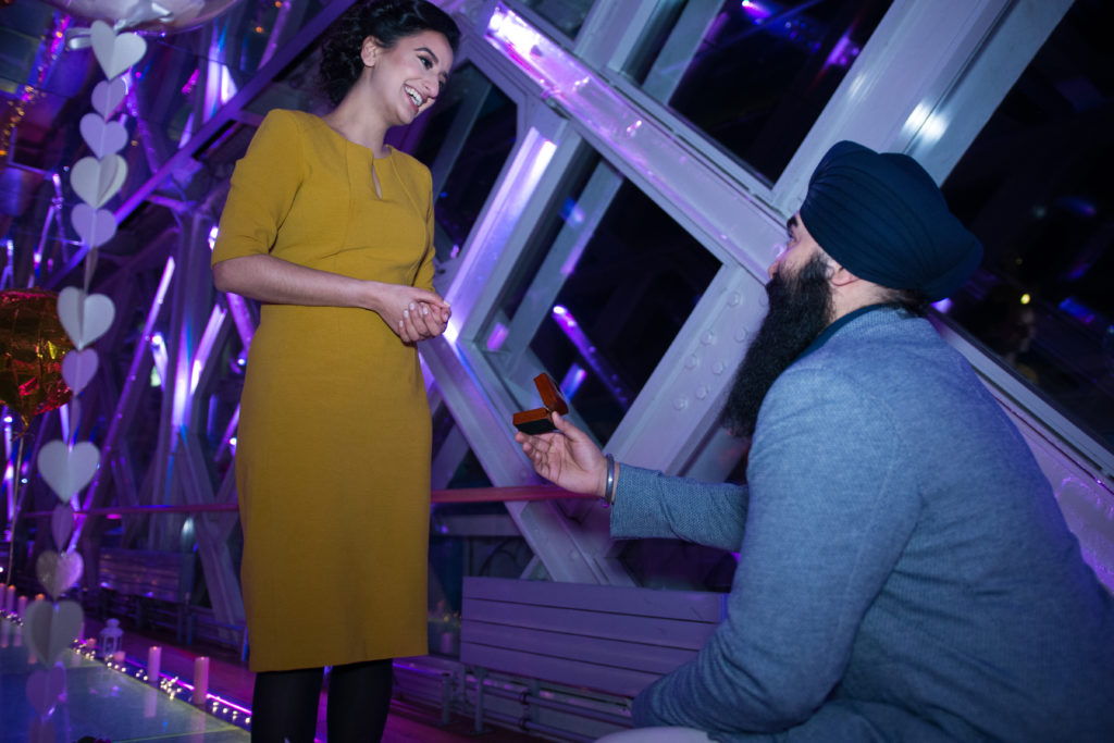 man down on one knee proposing to a woman in the walkways of Tower Bridge