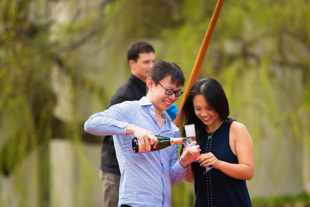 couple celebrating with champagne after their proposal in Cambridge