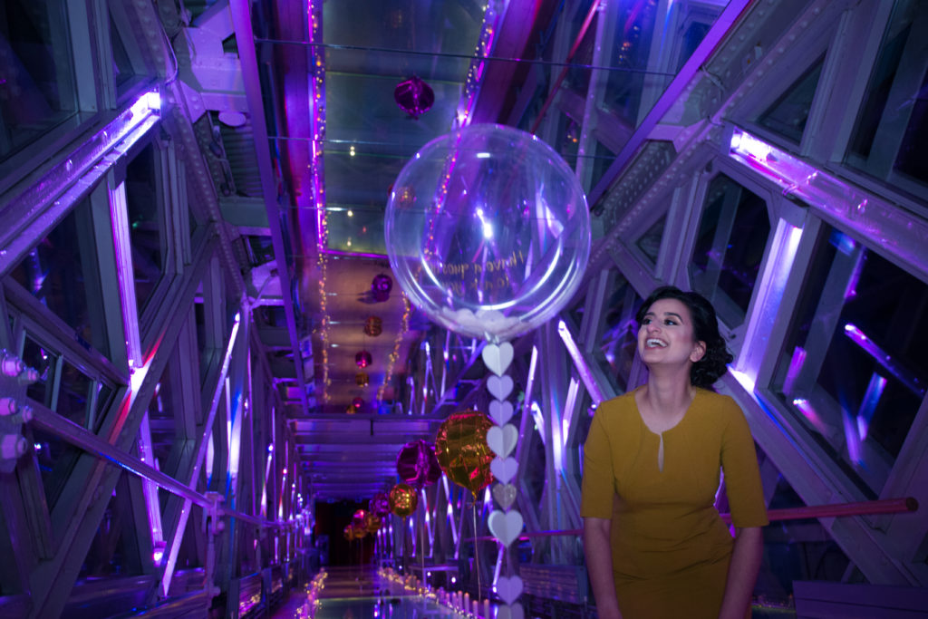 woman smiling whilst looking at a balloon in Tower Bridge