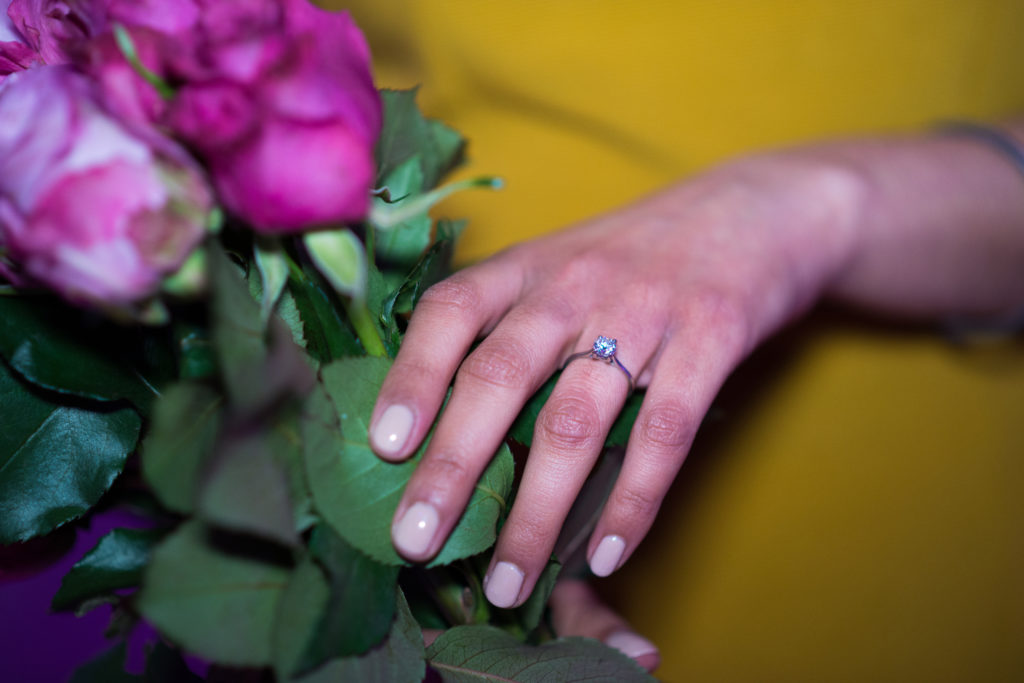 engagement ring next to roses