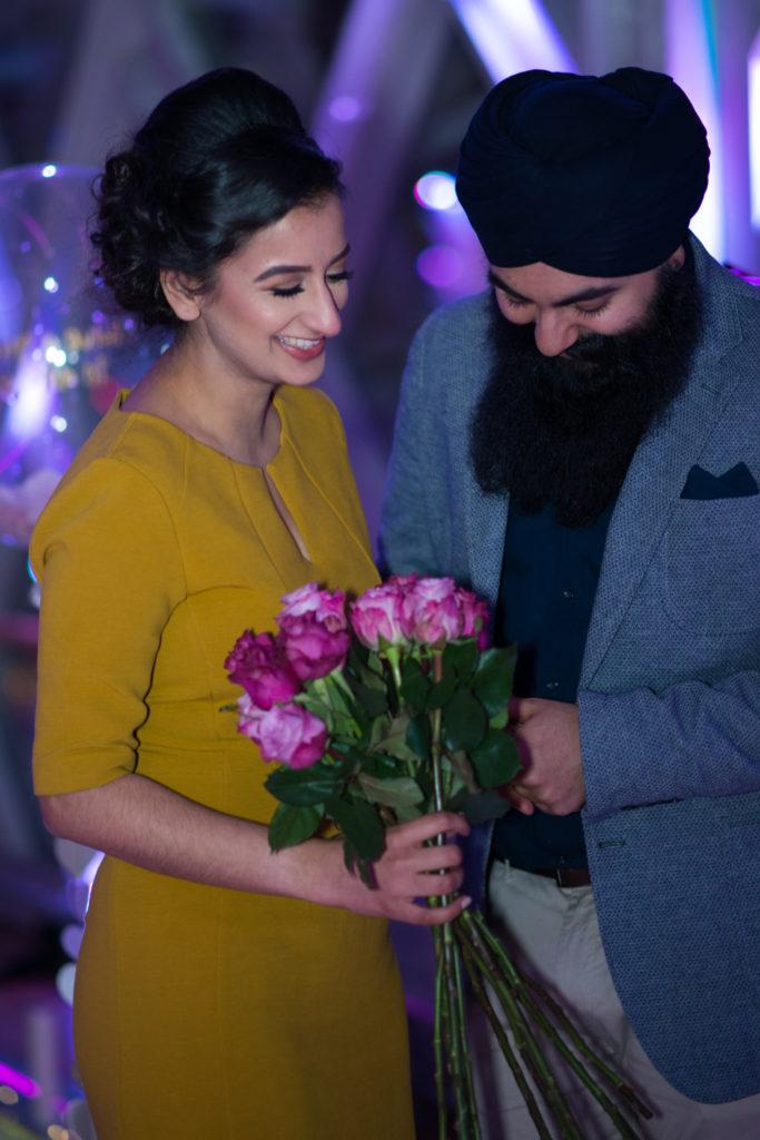 happy couple holding flowers in Tower Bridge