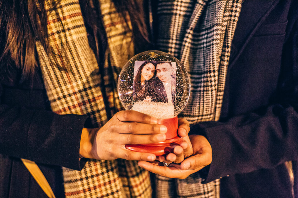 a couple holding a snow globe containing a photograph of the couple