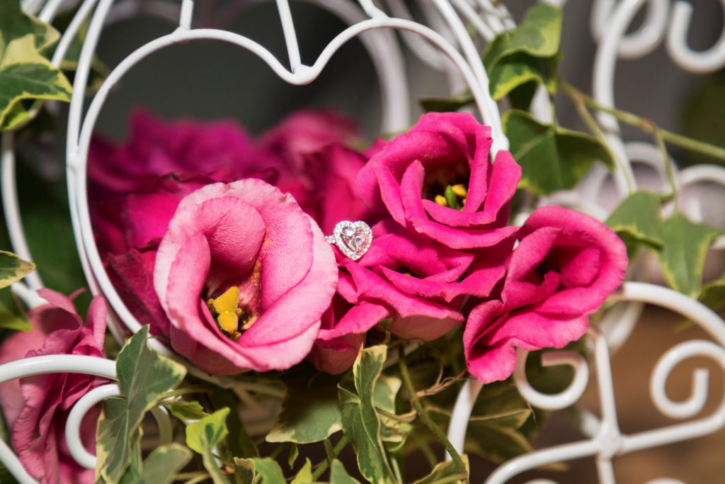 heart shaped diamond ring on a bed of roses